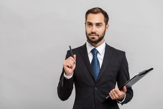 Atrakcyjny, zamyślony młody biznesmen w garniturze stojący na białym tle nad szarą ścianą, trzymający notatnik
