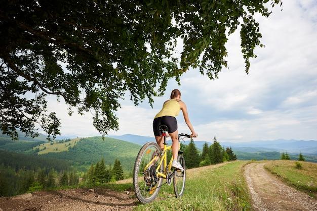 Atrakcyjny żeński cyklista z żółtym halnym bicyklem, cieszy się słonecznego dzień w górach