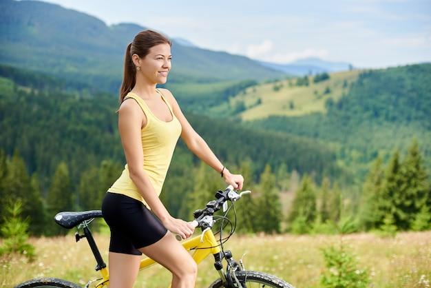 Atrakcyjny żeński rowerzysta z żółtym halnym bicyklem, cieszy się słonecznego dzień w górach