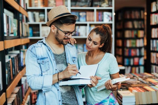 Atrakcyjnych młodych studentów mężczyzna i kobieta wybierając książki w księgarni.
