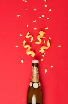 Atrybuty imprezowe wylatują z butelki wina szampańskiego na czerwonym tle