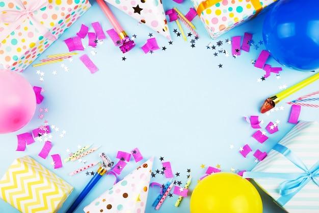 Atrybuty urodzinowe. kolorowe kulki, konfetti, prezenty, świeczki na ciasto. niebieskie tło. widok z góry. skopiuj miejsce