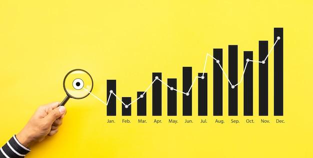 Audyt biznesowy i raport zysków z osobą trzymającą lupę z wykresem sukcesu. informacje i dane