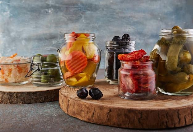 Auerkraut, marynowana marchewka, kiszone ogórki, marynowane oliwki i oliwki, suszone pomidory w szklanych słoikach