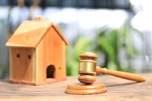 Aukcja nieruchomości, drewniany dom z młotkiem i model na naturalnym zielonym tle
