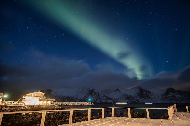Aurora borealis lub zorza polarna nad zaśnieżoną górą z oświetleniem domu w mefjord brygge, wyspa senja, norwegia