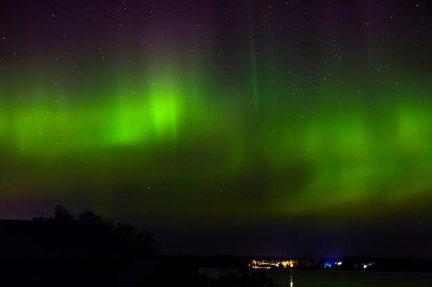 Aurora borealis nad miastem na wybrzeżu. światła polarne w nocy gwiaździste niebo nad jeziorem.