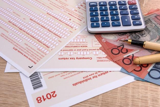 Australijski formularz podatkowy z długopisem, kalkulatorem i dolarami australijskimi