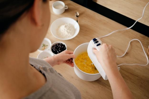 Autentyczna kobieta za pomocą ręcznego miksera