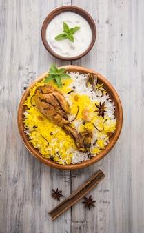Autentyczne biryani z kurczaka podawane w misce lub talerzu na kolorowym lub drewnianym tle. to pyszny przepis na ryż basmati zmieszany z pikantnym marynowanym kurczakiem, podawany z sałatką. selektywne skupienie
