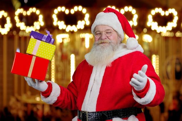 Autentyczny mikołaj trzyma prezenty świąteczne.