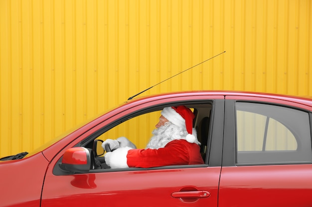 Autentyczny święty mikołaj jadący swoim czerwonym samochodem na żółtym tle