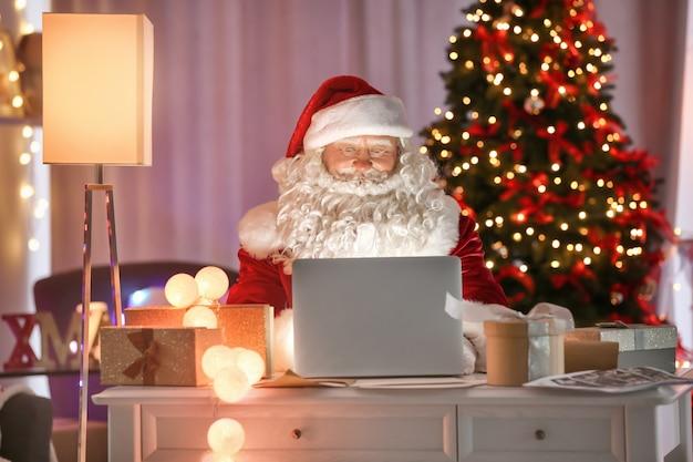 Autentyczny święty mikołaj używający laptopa przy stole w pokoju udekorowanym na boże narodzenie