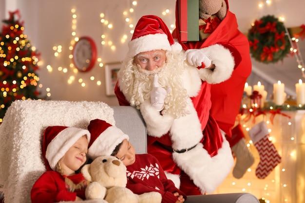 Autentyczny święty mikołaj w pobliżu śpiących dzieci w pokoju z pięknymi dekoracjami świątecznymi