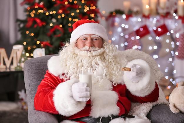 Autentyczny święty mikołaj z ciastkiem i szklanką mleka siedzi w fotelu w pokoju udekorowanym na boże narodzenie