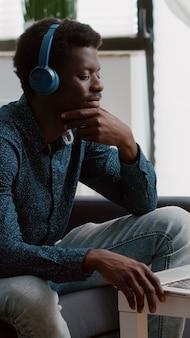 Autentyczny uśmiechnięty afroamerykanin używający laptopa ze słuchawkami do pracy w domu