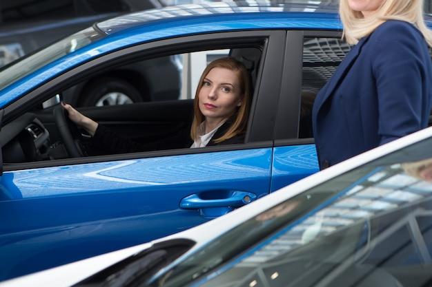 Auto biznes, sprzedaż samochodów, konsumpcjonizm i koncepcja ludzi - szczęśliwa kobieta z dealerem samochodowym w salonie samochodowym lub salonie