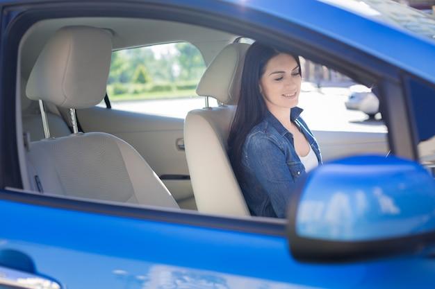 Auto kierowca. pozytywna miła brunetka kobieta siedzi w swoim samochodzie i trzyma kierownicę podczas jazdy
