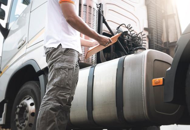 Auto mechanic driver trzyma schowek sprawdza inspekcję i konserwację zbiornika paliwa naczepy!