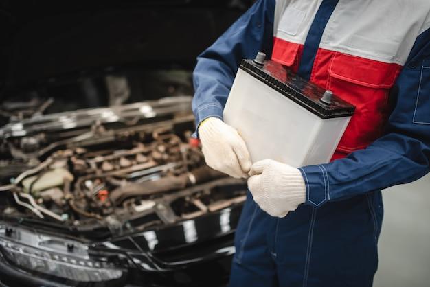 Auto mechanic ma zamiar wymienić nową baterię dla klientów, którzy korzystają z usługi wymiany baterii w sklepie.