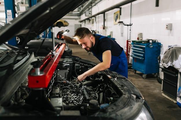 Auto mechanik łapiący silnik samochodu