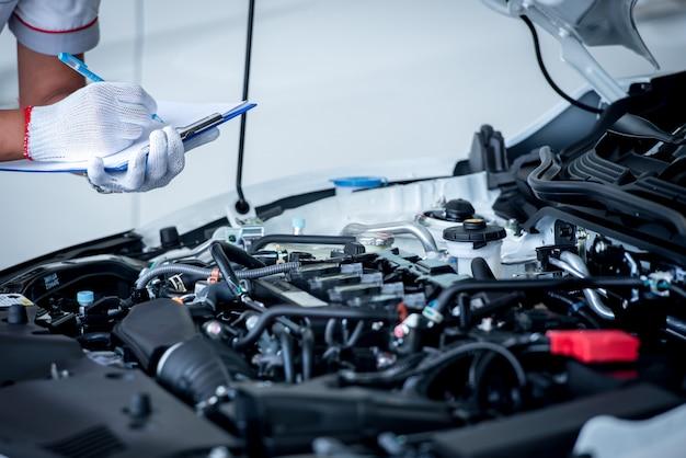 Auto mechanik (lub technik) sprawdzający silnik samochodu w garażu