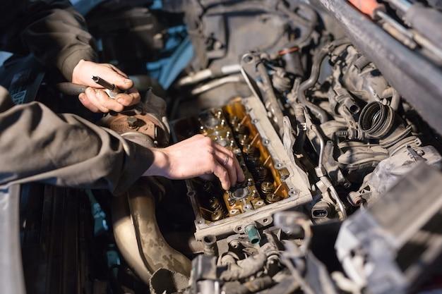 Auto mechanik pracuje w garażu. serwis naprawczy.