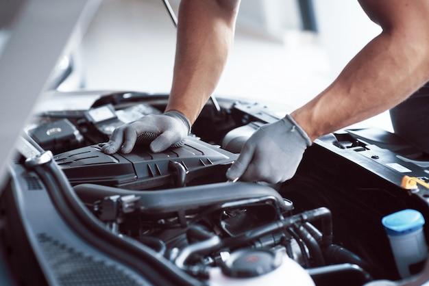 Auto mechanik pracuje w garażu. serwis naprawczy