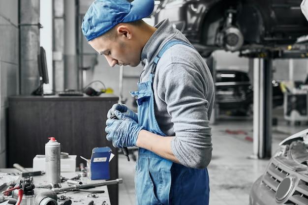 Auto mechanik pracuje w pobliżu stołu z różnymi narzędziami