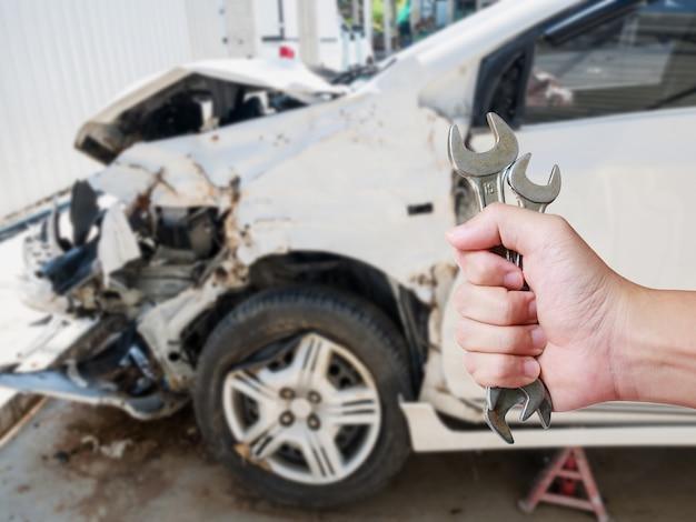 Auto mechanik ręczny klucz z uszkodzeniem samochodu w tle wypadek samochodowy koncepcja naprawy nadwozia