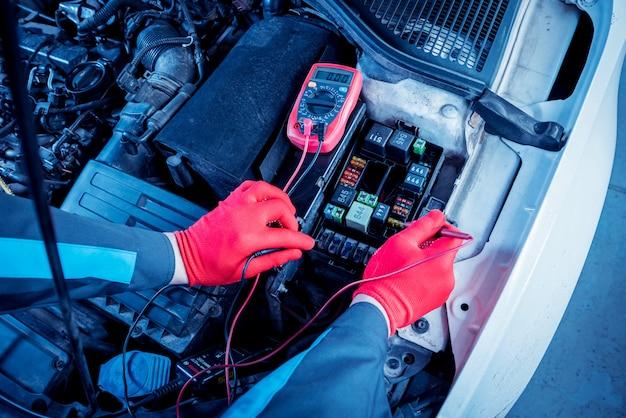 Auto mechanik używa woltomierza do sprawdzenia poziomu napięcia.