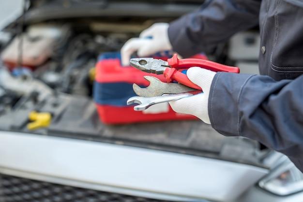 Auto mechanik w naprawie samochodów trzymając klucz i narzędzia. diagnostyka samochodowa