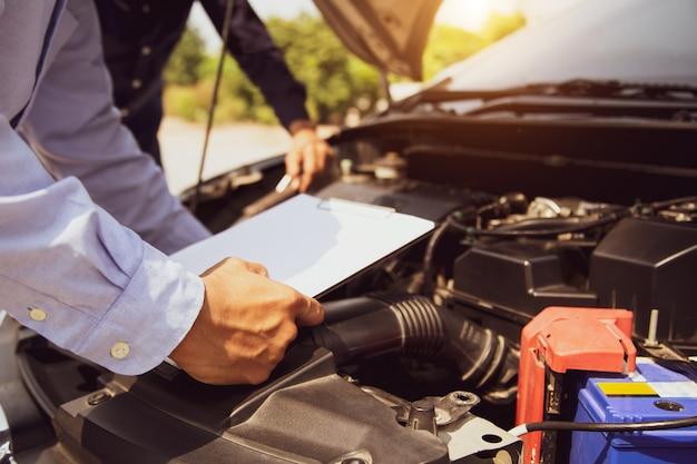 Auto mechanik za pomocą listy kontrolnej układów silnika samochodu po naprawieniu.