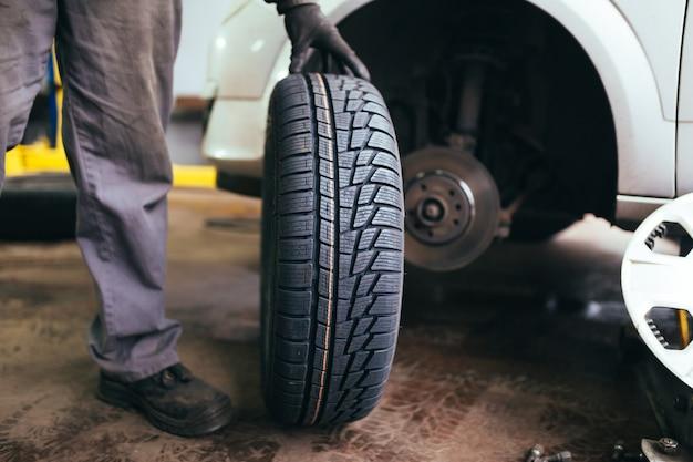 Auto mechanik zmienia koło w samochodzie.