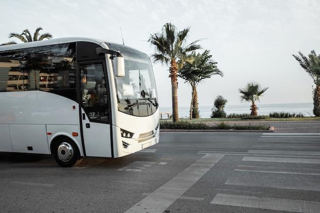 Autobus jeździ po drodze, wzdłuż brzegu morza, pojęcie wakacji, wypoczynku, transportu turystów, wycieczek.