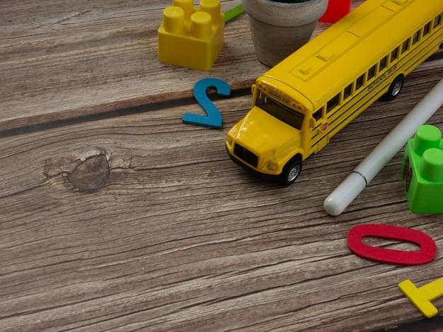 Autobus szkolny na drewnianym stole do edukacji lub koncepcji powrotu do szkoły