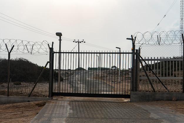 Automatyczna brama metalowa. drogę blokuje ogrodzenie z drutu kolczastego. brama na teren zamknięty.