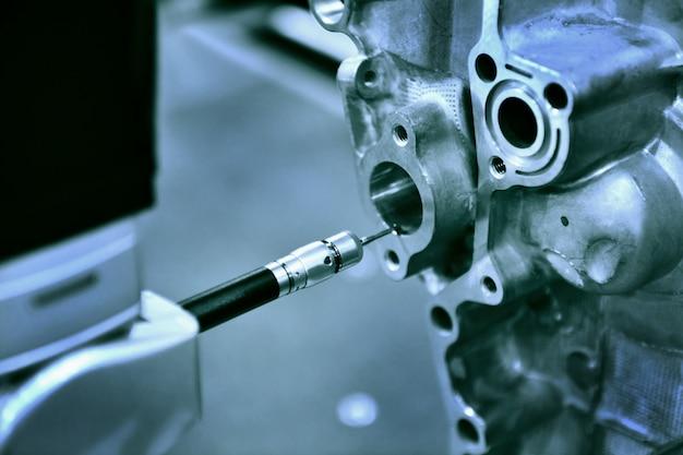 Automatyczna maszyna do pomiaru współrzędnych (cmm) z bliska do kontroli części o wysokiej precyzji podczas pracy, niebieski odcień