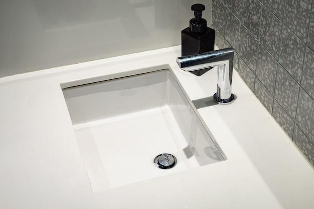 Automatyczny mikser wody nad białą umywalką z bliska
