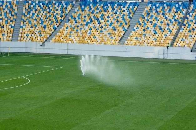 Automatyczny system nawadniania trawnika na stadionie. piłka nożna, boisko do piłki nożnej w małym prowincjonalnym miasteczku