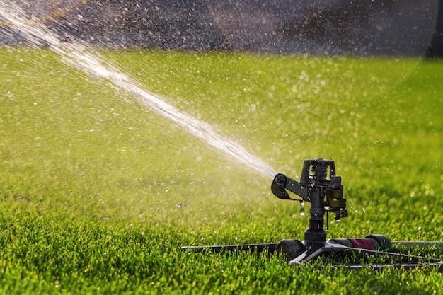 Automatyczny zraszacz do trawnika podlewający zieloną trawę na stadionie. system irygacyjny.
