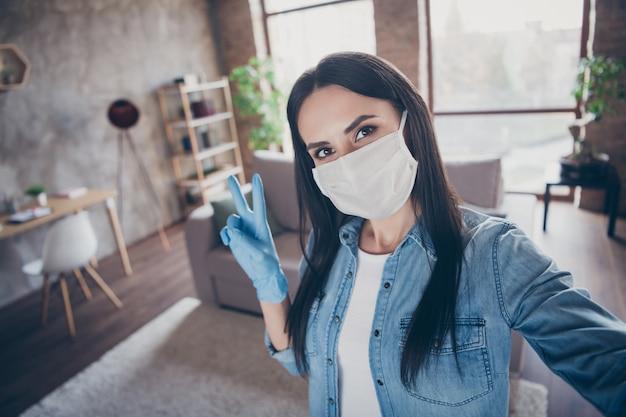 Autoportret jej ładnej atrakcyjnej uroczej brunetki w rękawiczkach z maską środki sanitarne pokazujący vsign wypoczynek wolny czas opieka zdrowotna w nowoczesnym loftowym ceglanym mieszkaniu przemysłowym