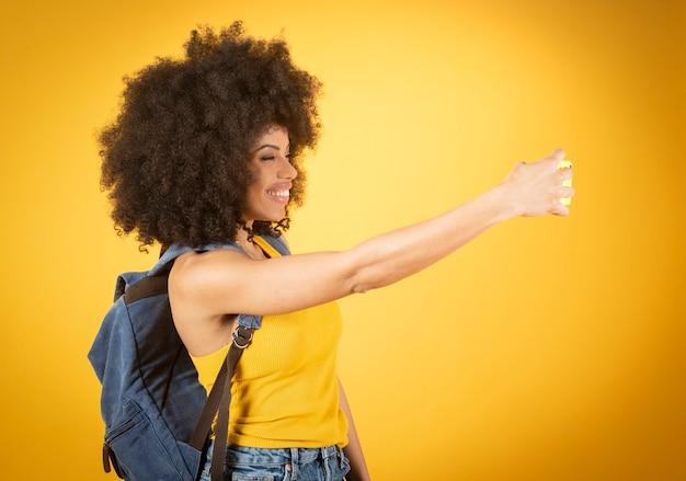 Autoportret pięknej młodej afroamerykanki robiącej znak pokoju.