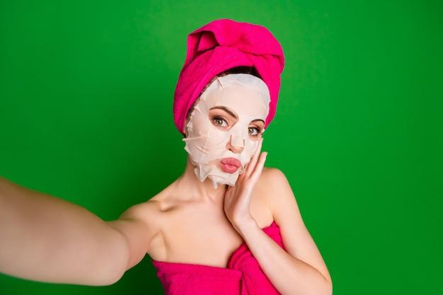 Autoportret pięknej nagiej kobiecej czarującej damy noszącej turbanową maskę na twarz, cieszącej się dotykaniem ust wydętych na białym tle na jasnozielonym tle