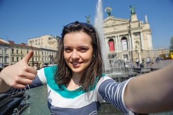 Autoportret rozochocona dziewczyna pokazuje kciuk up w starym mieście