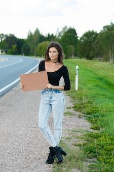 Autostopowicz na drodze trzyma pusty kartonowy znak