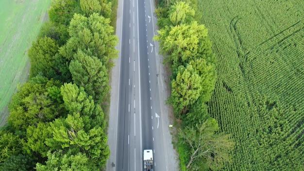 Autostradą jedzie ciężarówka z kontenerem. strzelanie z quadkoptera nad kremem drzew.