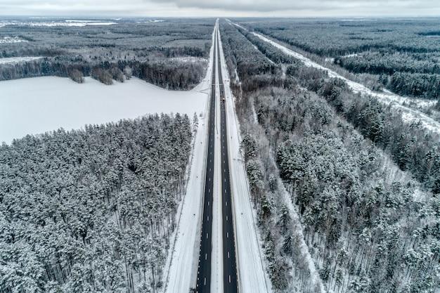 Autostrada przechodząca przez zimowy las. droga prowadzi do linii horyzontu.