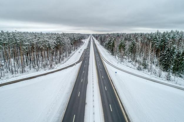 Autostrada przechodząca przez zimowy las.