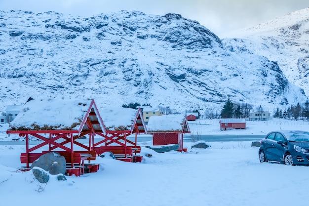 Autostrada wśród gór zimą w norwegii. dużo śniegu. pergole z tradycyjnymi dachami z trawy